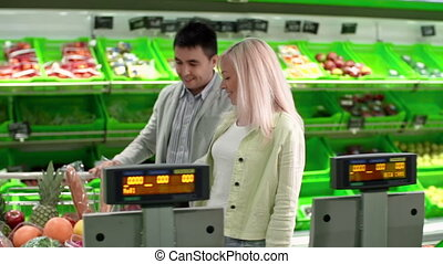Market Weight - Couple at self-service supermarket weighing...