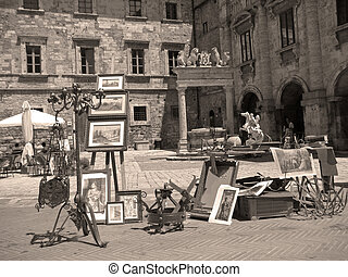 market with antiquities on main piazza of tuscan town, ...