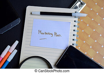 marketing plan written on paper isolated on black table