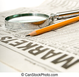 Newspaper open to market section wit tools for research, pencil and magnifying glass