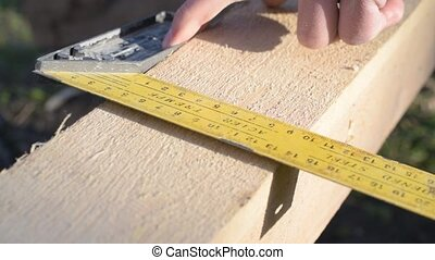 Marking a wooden beam with a pencil outdoors for cutting.