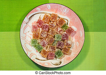 Marmalade colored candy on a ornate plate