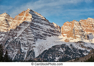 Maroon Bells mountains in snow at sunrise