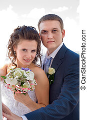 Groom embracing his bride. Focus point on the faces.