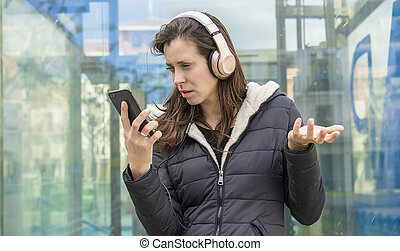 marriage, jealousy and suspicion in the cell phone, couple problems, adult woman looking at suspicious messages on the phone while on the street listening to music with headphones