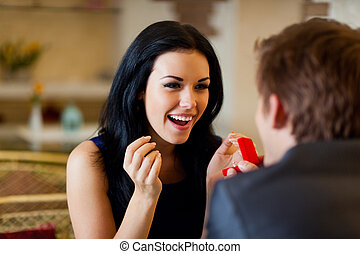 marriage proposal, man give ring to his girl, young happy couple romantic date at restaurant, celebrating valentine day