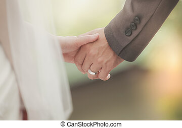 Married bride and groom holding hands as a symbol of love