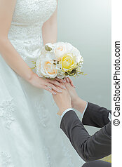 Married bride and groom holding hands with a bouquet of flowers as a symbol of love
