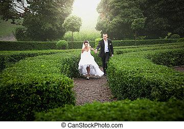 Married bride and groom running at garden maze
