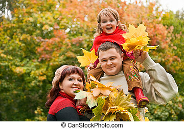 Married couple and little girl collect maple leafs In park...