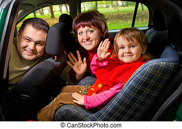 Married couple and  little girl  Greeting to wave hands in car in park