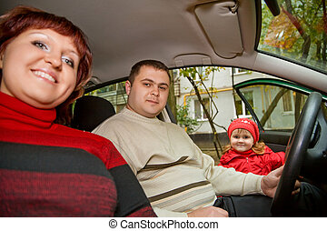 Married couple and  little girl sit in car near a building