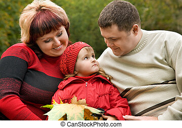Married couple and little girl sit on a bench in park in autumn