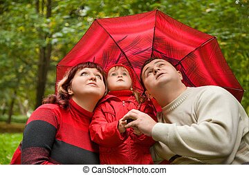 Married couple and  little girl with umbrella in park