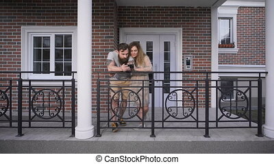 Married couple at doors of the brick house.