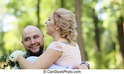 Married couple dance at sunny day. The groom lifts the bride and turns her