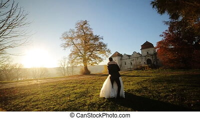 Married couple dance at sunset. The groom lifts the bride and turns her shot in slow motion  close up