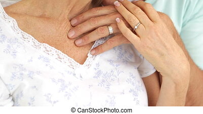 Married couple embracing and smiling at camera in bed...