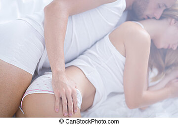Married couple embracing in bed at the morning