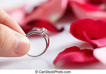 couple holding diamond ring