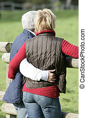 Married couple hugging by wooden fence