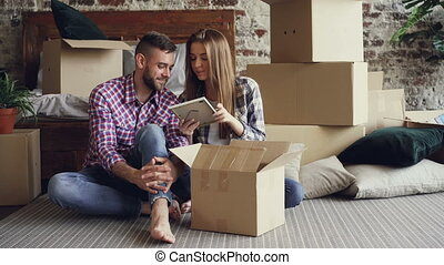 Married couple is unpacking personal things while sitting on...