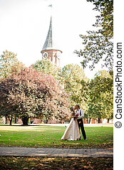 Married couple kissing on a green grass field with trees and old cathedral in background
