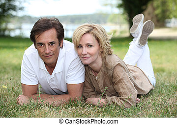 Married couple laying in the grass