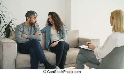 Married couple listening professional psychologist and trying to solve relationship porblems during visit psychotherapist office