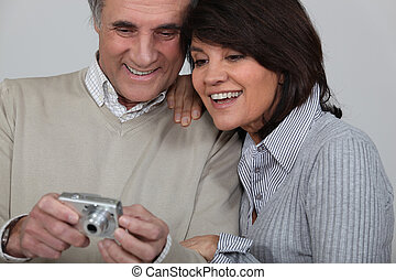 Married couple looking at photographs taken on digital camera