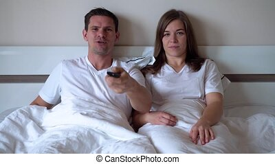 Married Couple Lying On The Bed And Watch Tv
