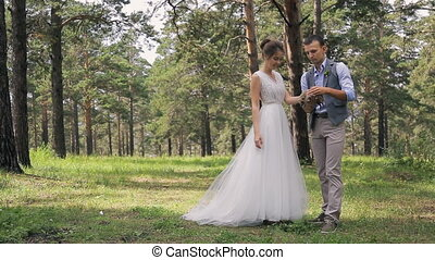 Married couple on photo shoot with hedgehog in hands on wedding day