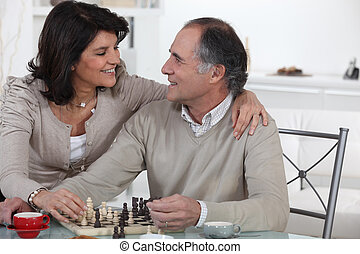 Married couple playing chess at home