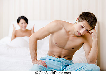 Married couple quarrels in bed. Depressed man sitting on the...