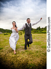 Married couple running and jumping in park while holding...