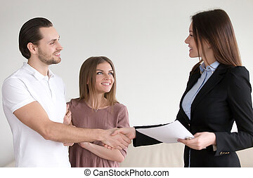 Married couple shaking hands with estate agent in new home -...
