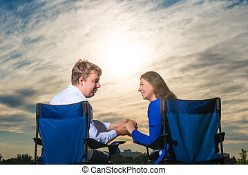 married couple sitting in chairs at dawn