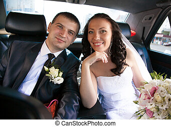 Married couple sitting on back seat of car and looking at camera