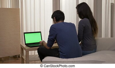 Married couple sitting on the couch with a laptop deciding what to buy online at home in living room