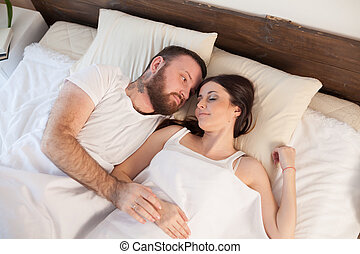 married couple sleeping in the bedroom