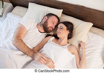married couple sleeping in the bedroom