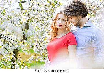 Married couple spending leisure time in the orchard -...