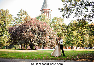 Married couple standing on a green grass field with trees and old cathedral in background