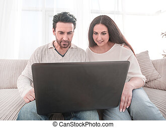 married couple watching a show on their laptop