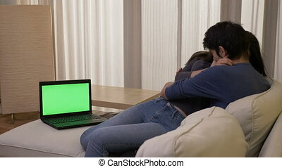 Married couple watching a thriller movie in the living, room on a laptop with green screen hugging and laughing