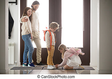 Married couple with children in hallway at home