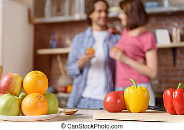 Married couple with healthy food in kitchen