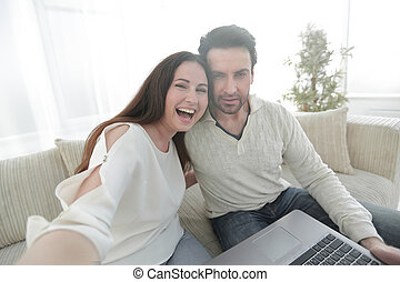 married couple with laptop sitting on the couch