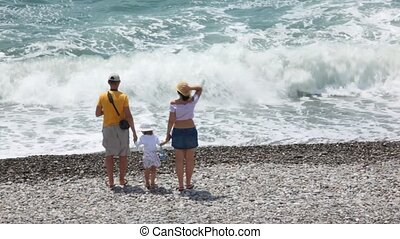married couple with their little daughter looking at waving sea