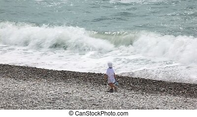 married couple with their little daughter walking on pebble beach